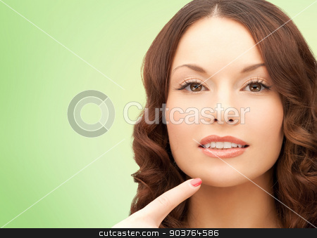 beautiful young woman pointing finger to her chin stock photo, beauty, people and health concept - beautiful young woman pointing finger to her chin over green background by Syda Productions