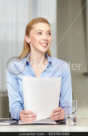 smiling woman holding papers in office stock photo, business and people concept - smiling woman holding papers in office by Syda Productions