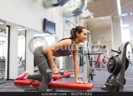 happy woman with dumbbell flexing muscles in gym stock photo, fitness, sport, training and people concept - smiling woman with dumbbell flexing muscles on bench in gym by Syda Productions