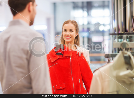 happy young couple choosing clothes in mall stock photo, sale, shopping, consumerism and people concept - happy young couple choosing clothes at clothing store in mall by Syda Productions
