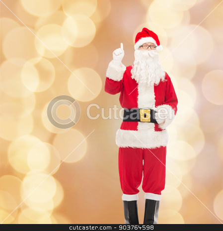 man in costume of santa claus stock photo, christmas, holidays, gesture and people concept - man in costume of santa claus pointing finger up over beige lights background by Syda Productions