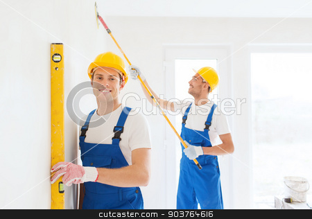 group of builders with tools indoors stock photo, building, teamwork and people concept - group of smiling builders in hardhats with tools indoors by Syda Productions