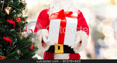 man in costume of santa claus with gift box stock photo, christmas, holidays and people concept - close up of santa claus with gift box and tree over lights background by Syda Productions