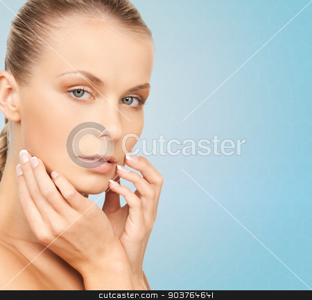 beautiful young woman face stock photo, beauty, people and health concept - beautiful young woman touching her face over blue background by Syda Productions