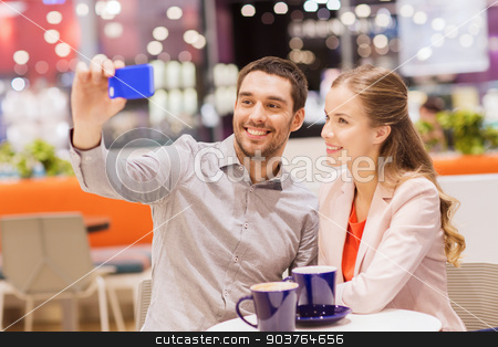 happy couple with smartphone taking selfie in mall stock photo, sale, shopping, consumerism, technology and people concept - happy young couple with smartphone taking selfie at cafe in mall by Syda Productions