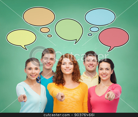 group of smiling teenagers with text bubbles stock photo, school, education, communication and people concept - group of smiling teenagers over green board background with text bubbles by Syda Productions