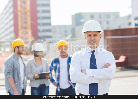 group of smiling builders in hardhats outdoors stock photo, business, building, teamwork and people concept - group of smiling builders in hardhats outdoors by Syda Productions