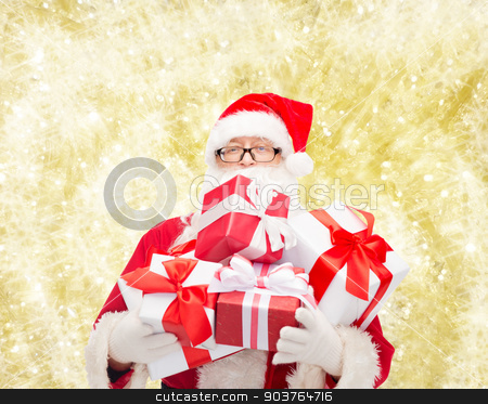 man in costume of santa claus with gift boxes stock photo, christmas, holidays and people concept - man in costume of santa claus with gift boxes over yellow lights background by Syda Productions