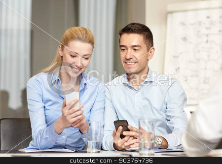 smiling business people with smartphones in office stock photo, business, people and technology concept - smiling business team with smartphones meeting in office by Syda Productions
