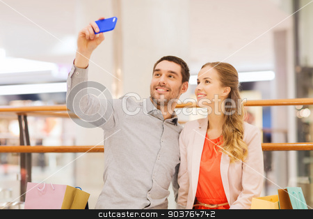 happy couple with smartphone taking selfie in mall stock photo, sale, consumerism, technology and people concept - happy young couple with shopping bags and smartphone taking selfie in mall by Syda Productions
