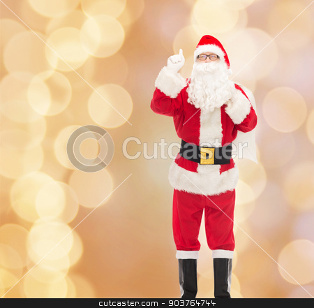 man in costume of santa claus with bag stock photo, christmas, holidays, gesture and people concept - man in costume of santa claus with bag pointing finger up over beige lights background by Syda Productions