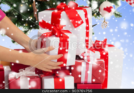 close up of woman with gifts and christmas tree stock photo, winter holidays, celebration and people concept - close up of woman putting present under christmas tree over blue background with snow by Syda Productions
