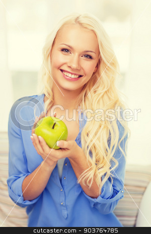 smiling woman with green apple at home stock photo, diet, health and home concept - smiling yoing woman with green apple at home by Syda Productions