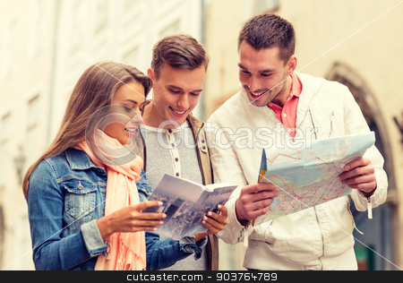 group of smiling friends with city guide and map stock photo, travel, vacation and friendship concept - group of smiling friends with city guide and map exploring city by Syda Productions