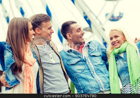 group of smiling friends in amusement park stock photo, leisure, amusement park and friendship concept - group of smiling friends ferris wheel on the back by Syda Productions