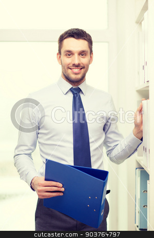 handsome businessman picking folder at office stock photo, business and office concept - handsome businessman holding folder and picking another one at office by Syda Productions