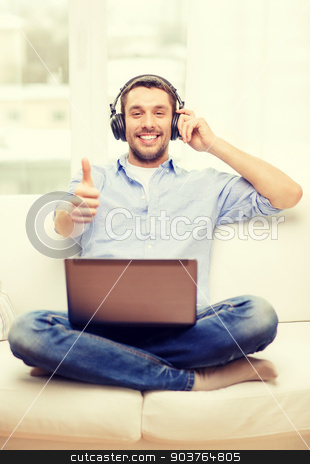 smiling man with laptop and headphones at home stock photo, technology, home, music and lifestyle concept - smiling man with laptop and headphones at home showing thumbs up by Syda Productions