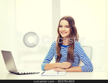 smiling teenage girl laptop computer and notebook stock photo, education, technology and home concept - smiling teenage girl with laptop computer, notebook and pen at home by Syda Productions