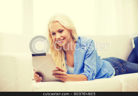 smiling woman with tablet pc computer at home stock photo, home, technology and internet concept - smiling woman lying on the couch with tablet pc computer at home by Syda Productions