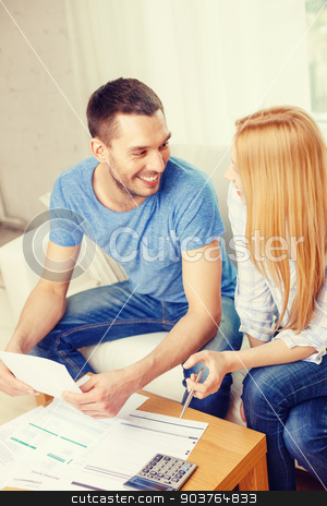 smiling couple with papers and calculator at home stock photo, tax, finances, family, home and happiness concept - smiling couple with papers and calculator at home by Syda Productions
