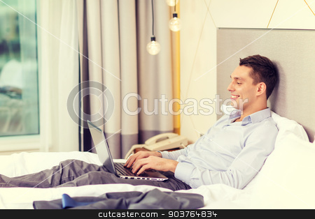 happy businesswoman with laptop in hotel room stock photo, business, technology, internet and hotel concept - happy businessman with laptop computer lying in hotel in bed by Syda Productions