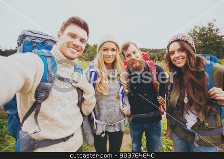 group of smiling friends with backpacks hiking stock photo, adventure, travel, tourism, hike and people concept - group of smiling friends with backpacks making selfie outdoors by Syda Productions
