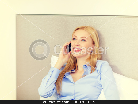 happy businesswoman with smartphone in hotel room stock photo, business, technology and hotel concept - happy businesswoman with smartphone lying in hotel in bed by Syda Productions