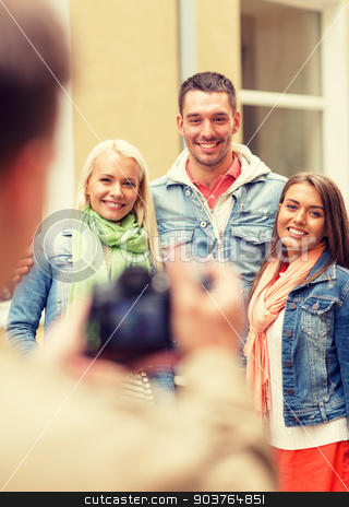 group of smiling friends taking photo outdoors stock photo, travel, vacation, technology and friendship concept - guy picturing group of friends in city by Syda Productions
