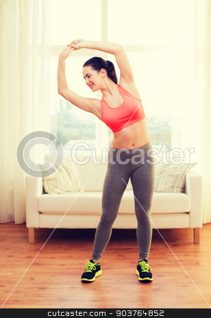 smiling teenage girl streching at home stock photo, fitness, home and diet concept - smiling teenage girl streching at home by Syda Productions