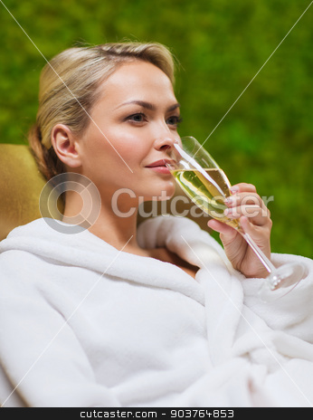 beautiful young woman drinking champagne at spa stock photo, people, beauty, lifestyle, holidays and relaxation concept - beautiful young woman in white bath robe lying on chaise-longue and drinking champagne at spa by Syda Productions
