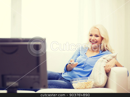 young girl with popcorn watching movie at home stock photo, food, happiness and people concept - smiling young girl with popcorn watching movie at home by Syda Productions