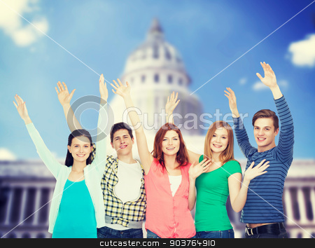 group of smiling students waving hands stock photo, education and people concept - group of smiling students standing and waving hands by Syda Productions