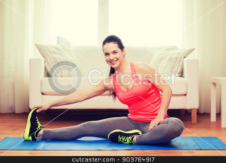 smiling teenage girl streching on floor at home stock photo, fitness, home and diet concept - smiling teenage girl streching on floor at home by Syda Productions
