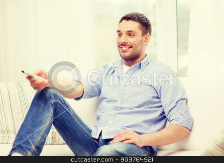 smiling man with tv remote control at home stock photo, home, technology and entretainment concept - smiling man with tv remote control at home by Syda Productions
