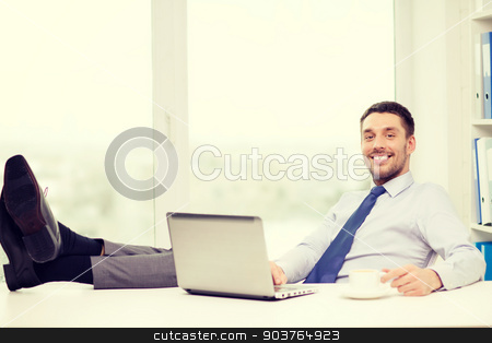 smiling businessman or student with laptop stock photo, office, business, education, technology and internet concept - smiling businessman or student with laptop computer and coffee at office by Syda Productions