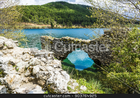 Stone Wall at Blue Lake in the mountains stock photo, Stone wall at a blue lake under a cloudy sky - landscape. by ANTONIOS KARVELAS