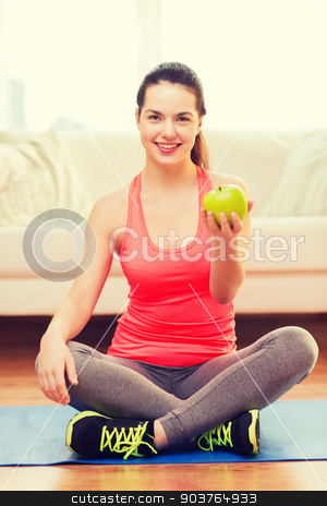smiling teenage girl with green apple at home stock photo, healt, dieting, home and happiness concept - smiling sporty teenage girl with green apple at home by Syda Productions
