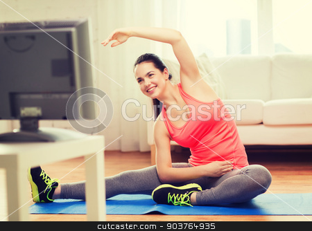 smiling teenage girl streching on floor at home stock photo, fitness, home and diet concept - smiling teenage girl streching on floor and watching tv at home by Syda Productions