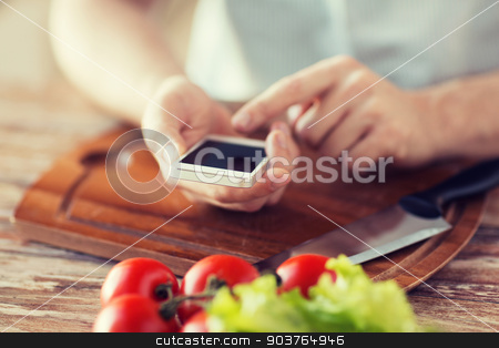 closeup of man pointing finger to smartphone stock photo, cooking, technology and home concept - closeup of man pointing finger to smartphone by Syda Productions