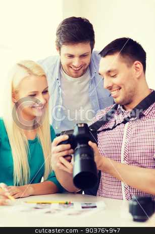 smiling team with photocamera working in office stock photo, business, education, office and startup concept - smiling creative team with photocamera working in office by Syda Productions