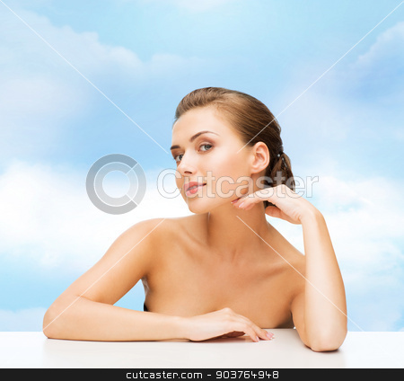 smiling woman with clean perfect skin stock photo, beauty, health and people concept - smiling beautiful woman with clean perfect skin over blue cloudy sky background by Syda Productions