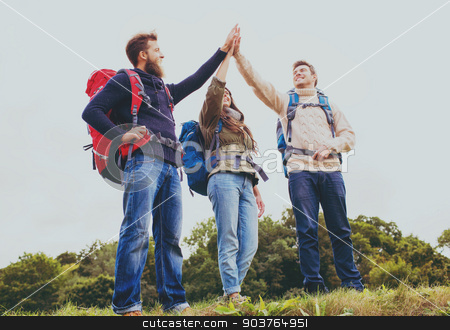 group of smiling friends with backpacks hiking stock photo, travel, tourism, hike, gesture and people concept - group of smiling friends with backpacks making high five outdoors by Syda Productions