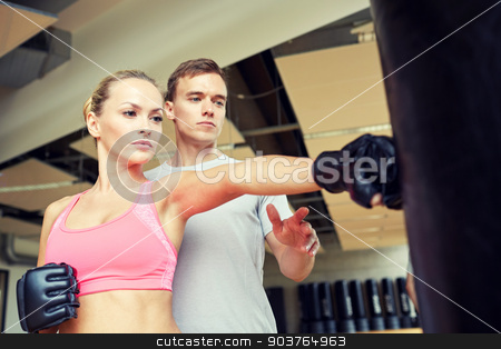 woman with personal trainer boxing in gym stock photo, sport, fitness, lifestyle and people concept - woman with personal trainer boxing punching bag in gym by Syda Productions