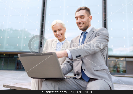 smiling businesspeople with laptop outdoors stock photo, business, education, technology and people concept - smiling businesspeople working with laptop computer on city street by Syda Productions
