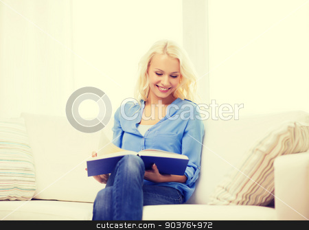 smiling woman reading book and sitting on couch stock photo, leasure and home concept - smiling middle-aged woman reading book and sitting on couch at home by Syda Productions