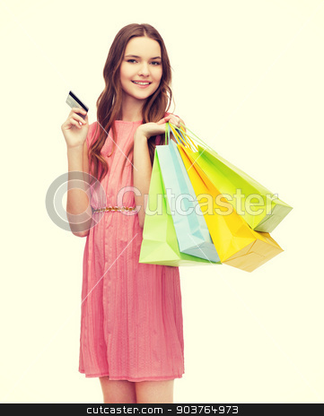 smiling woman in dress with many shopping bags stock photo, retail and sale concept - smiling woman in dress with many shopping bags and credit card by Syda Productions