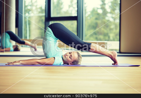 smiling woman stretching on mat in gym stock photo, fitness, sport, training and lifestyle concept - smiling woman stretching on mat in gym by Syda Productions