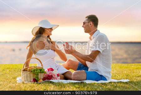 smiling couple with small red gift box on picnic stock photo, love, dating, people, proposal and holidays concept - smiling young man giving small red gift box with wedding ring to his girlfriend on picnic over seaside sunset background by Syda Productions