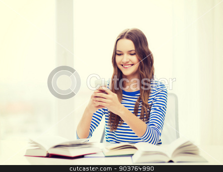 smiling student girl with smartphone and books stock photo, education, technology and home concept - happy smiling student girl with smartphone and books by Syda Productions