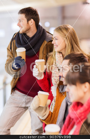 happy friends with coffee cups on skating rink stock photo, people, friendship, hot drinks and leisure concept - happy friends drinking from paper coffee cups on skating rink by Syda Productions